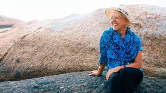 youthful women in blue scarf at beach with straw hat