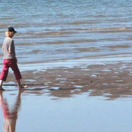 lady walking on beach at water