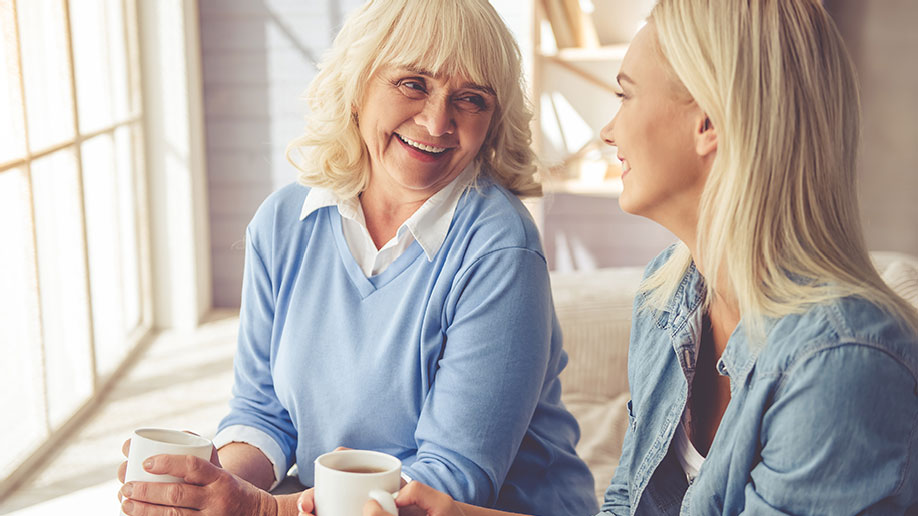Blonde mother and daughter chatting over tea