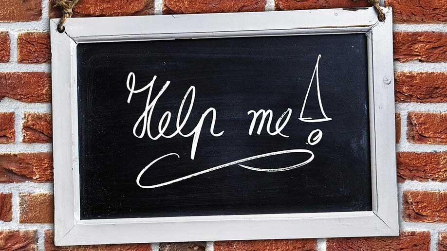 Help me blackboard sign on brick wall