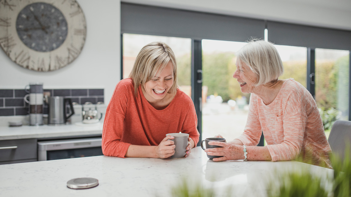 two ladies having tea and laughing in kitchen