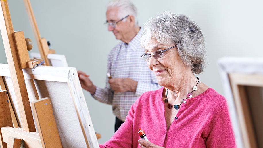 Grey haired lady with glasses and pink cardigan painting art class