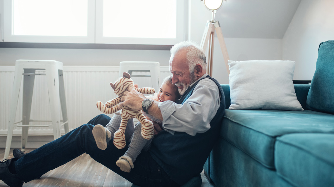 Grandfather holding toy giraffe playing with grand daughter