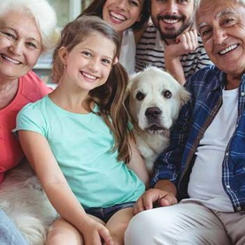 three generations of family on couch with family dog