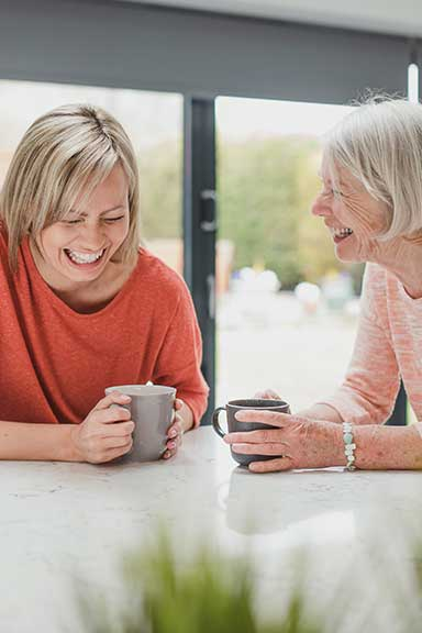 two women laughing over a coffee at home