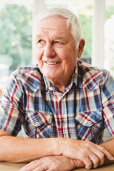 Man in chequer shirt glancing to side with smile
