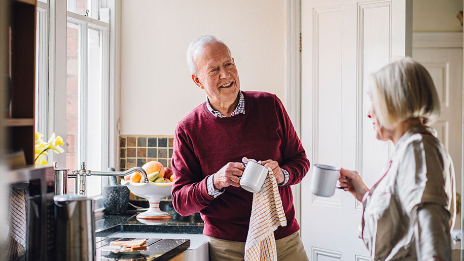 man drying a cup talking to his wife in kitchen