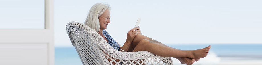woman with long grey hair reading with legs draped over chair at beach house